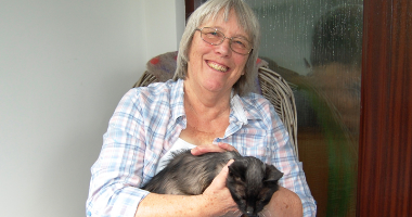 A woman smiling and stroking a cat