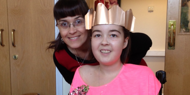 Mum and daughter wearing Christmas hat smiling to camera