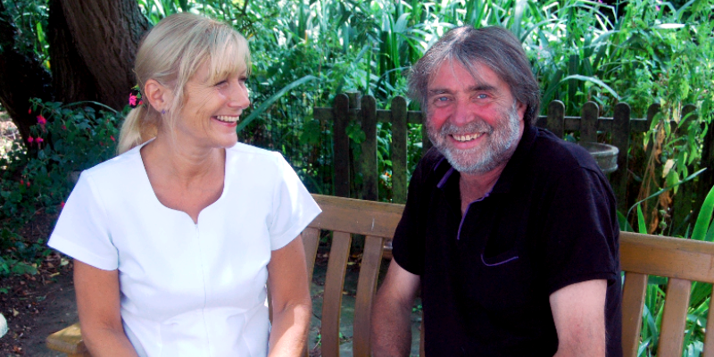 Roger sits with a nurse in the garden