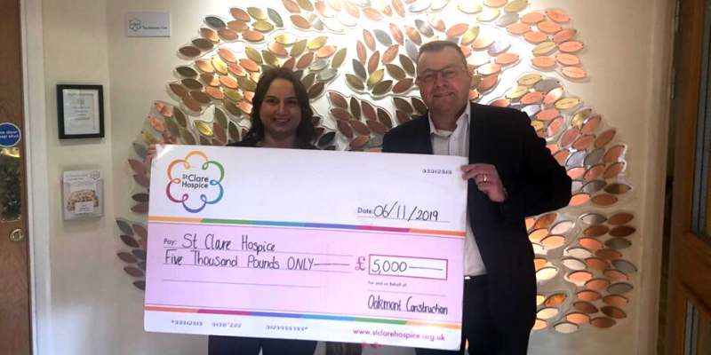 Amy and Andy holding a cheque being presented to St Clare