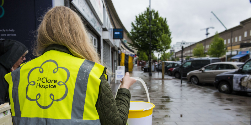 A woman in a high-vis St Clare jacket walks with a charity collection bucket in the street